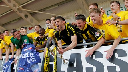 Burton Albion players lift the runners-up trophy after they are promoted from League One. Photo: Ric