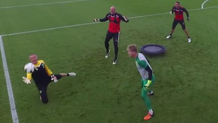 Norwich goalkeeping coach Dean Kiely dives for the ball in a game of Spikeball with Norwich City goa