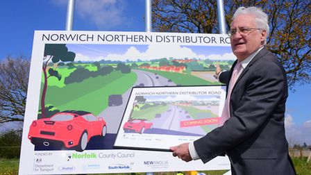 As work continues on the Norwich NDR, council leader George Nobbs unveils one of the new scheme boar