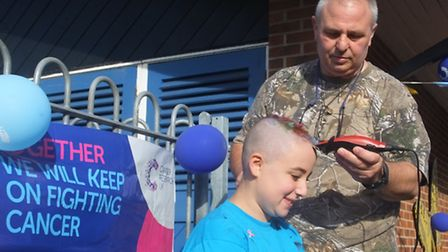 Genna Newman's dad Gary puts the finishing touches to his daughter's charity head shave. Picture: KA