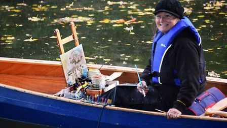 Artist Sue Mann at work paints from a canoe at Cow Tower during the Norwich Paint Out. Picture: DENI