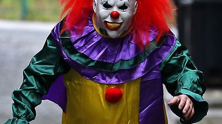 """POSED BY MODELA person wearing a clown costume in a street in Liverpool. The """"killer clown"""" craze ha"""