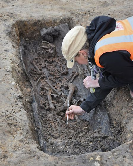 An archaeologist carefully excavates Anglo Saxon human remains and a dug-out coffin at the Wensum Pa