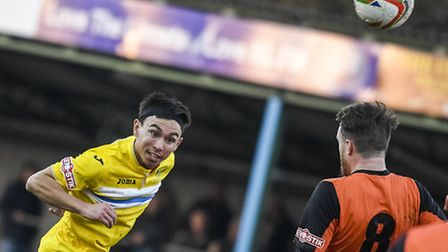 Action from King's Lynn Town v St Ives at The Walks in the FA Trophy Michael Clunan heads the ball.