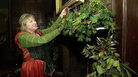 """Lady Emma Paine (Vera McLean) adjusts the decorations at Strangers Hall for """"her"""" Stuart Christmas."""