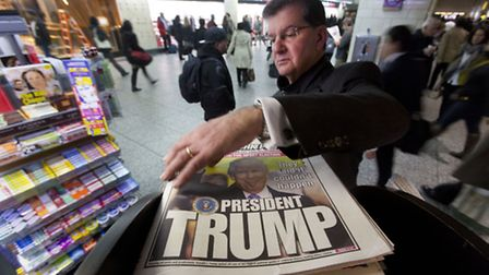 A man reaches for the New York Post newspaper featuring president-elect Donald Trump's victory. (AP