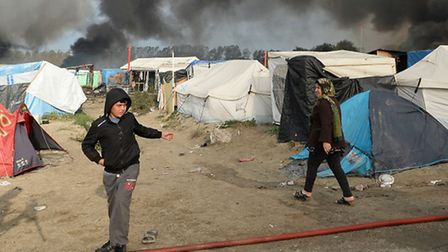 Smoke rises over the Calais Jungle camp, as several large fires broke out in the near deserted migra