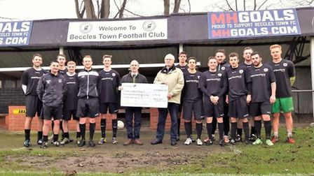 Chris Brown, cup lunch organiser and the Beccles Town first team present the cheque to Dr Anthony Bu