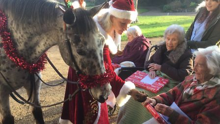Letheringsett Hall director Laura Smith and her horse Spotty Dot delivering presents to residents