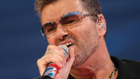 Singer, George Michael on stage performing at Norwich City Football Club ground at Carrow Road in No
