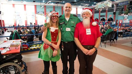Two committee members and volunteer dirver camouflauged as Santa at Open Christmas Dinner for the ho