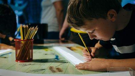 A boy uses the light table to creatre artworks, part of the interactive show that runs through the f