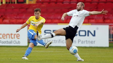 Russell Penn (r) of Gateshead FC attempts to block a shot from Toby Hilliard of King's Lynn Town FC