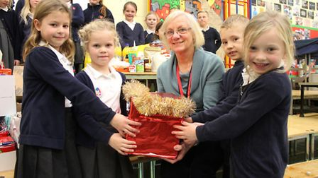 Sheringham Primary School pupils handing over some of the Christmas treats they collected to Cromer