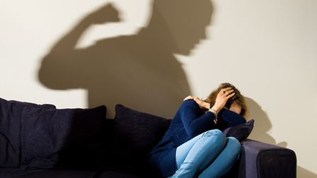 PICTURE POSED BY MODEL A shadow of a man with a clenched fist as a woman cowers in the corner. Photo