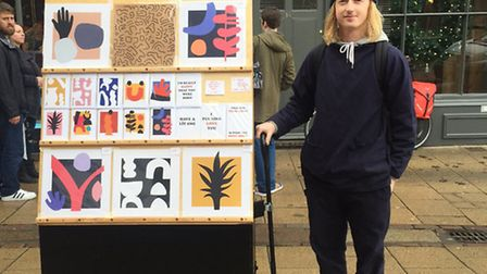 Art In A Cart, artist Sam Harrons is selling his work from a cart in Norwich Lanes. Here he can be s