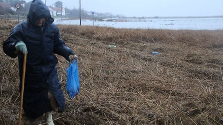 A Salthouse resident struggles to walk along the A149 Coast Road which is caked in debris dumped by