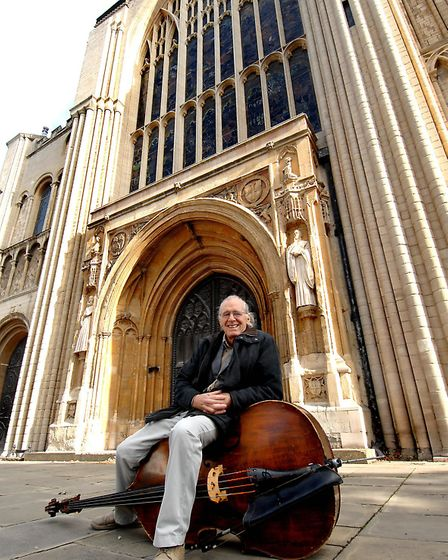 David Holgate, jazz musician and stonemason, at Norwich Cathedral where he carved the two figures ei