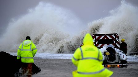 Rescue workers make their way into Walcott, near Great Yarmouth, as the east of England is hit by a