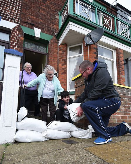 Terry Rawlinson and his son Jake, 11, put sandbags at the gate of their neighbours, Mary Powley and