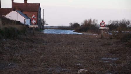 The main road through Salthouse was cut off by the sea after the storm surge. A sign in the distance
