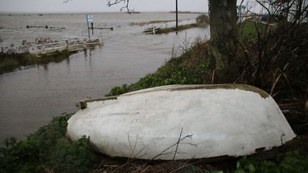 An upturned boat sits at the side of the Coast Road, close to the aptly named Beach Road bus stop. P