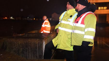Police and search and rescue officers watch the River Yare at it's highest point near the Haven Brid