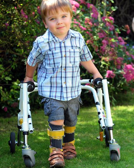 Blake Barley with his splints and walking frame. The three-year-old has cerebral palsy, and his pare