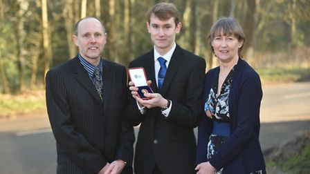 Sean Lott receives his gold medal from KES school presented by The Queen. Pictured with parents Alan