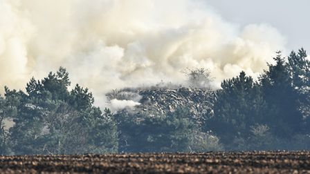 A fire continues to burn in a timber yard in North Runcton. Byline: Sonya Duncan Copyright: Archant