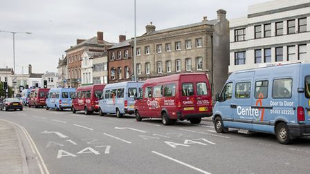 The fleet of Centre 81 buses passing through the town.