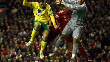 Norwich City's former striker Grant Holt heading the ball into the net against Liverpool at Anfield