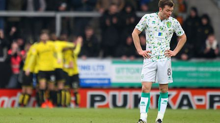 Norwich's Jonny Howson looks dejected as the Burton players celebrate their sides second goal durin