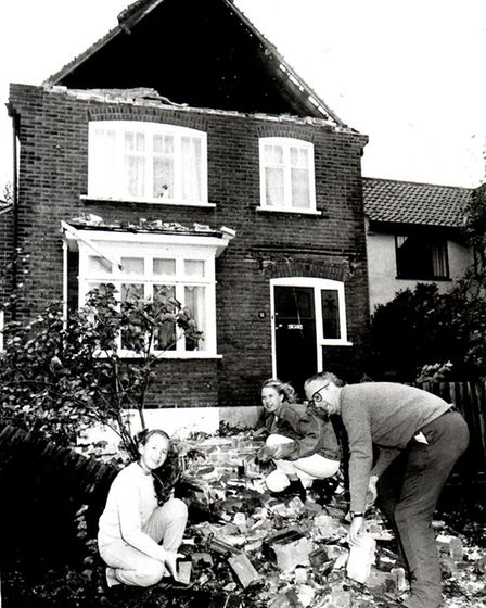 Chris Everett and his daughters, Alice, left, and Lucy try to clear up rubble at their home after th