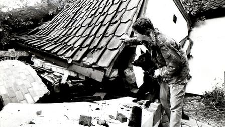 Kevin Last pictured with his dog, Lady, as he surveys the wrecked garage with father's flattened car