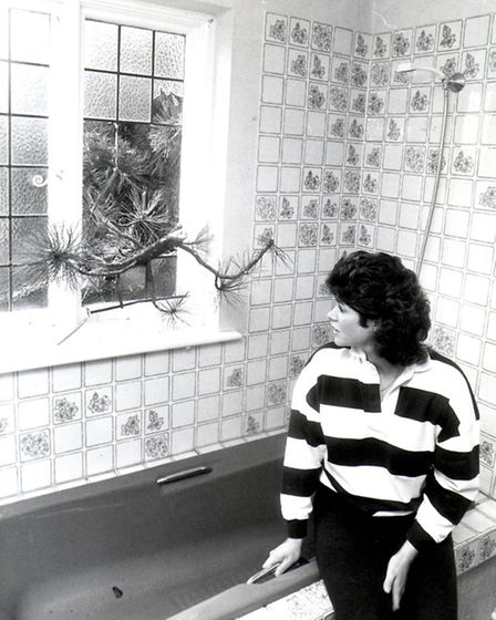 Lynn Spicer observes the tree that crashed through her bathroom window on Grange Road, Norwich. Phot