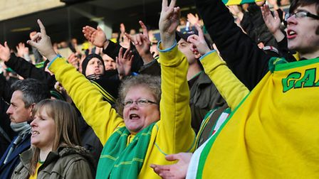 Dressed in the team colours, excitable fans cheer at npower Championship Norwich City Football Club