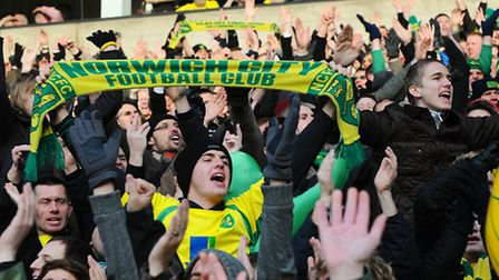 A fan waves his team scarf in the air at the npower Championship between Norwich City Football Club