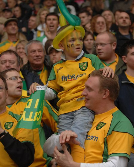 Sporting a green and yellow balloon hat, one young fan watches the game from a higher height at the