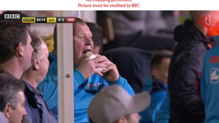 Caught on camera - Wayne Shaw tucks into his pie during Sutton's FA Cup tie against Arsenal. Photo: