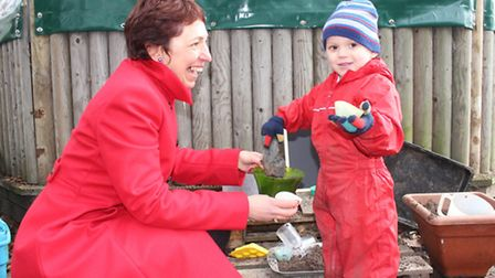 Executive head teacher Angie Hamilton has a go at mud pie making with three-year-old Harry, who is o