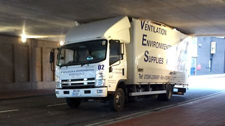 A bridge too low - a lorry trapped while trying to negotiate an underpass. Picture: PA