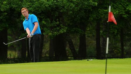 Aaron Bullock chips onto the 18th green during the Norfolk Amateur Golf Championship at Thetford Gol