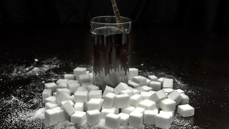 A cola carbonated drink surrounded by sugar cubes. Anthony Devlin/PA Wire