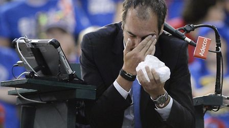 Umpire Arnaud Gabas, of France, holds his face after being hit by a ball during first-round Davis Cu