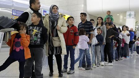 Refugees from Syria and Iraq stand in a queue at the Athens International airport during a relocatio