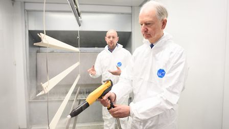 Sir Henry Bellingham with Jack Thompson, left, trying out the new powder coating facility at the Wr