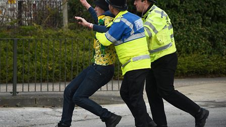 Police usher a NCFC fan away from the ground after the NCFC v Ipswich Town FC derby match.Picture: