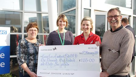 Maggie and Russell Clarke present the cheque to Macmillan information and support manager Vicky Mitc