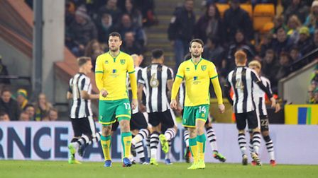 Yanic Wildschut and Wes Hoolahan look dejected as the Newcastle players celebrate their sides rapid